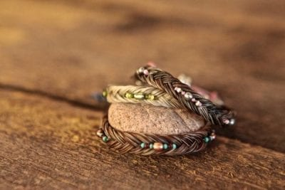 beaded braided bracelets over river stone